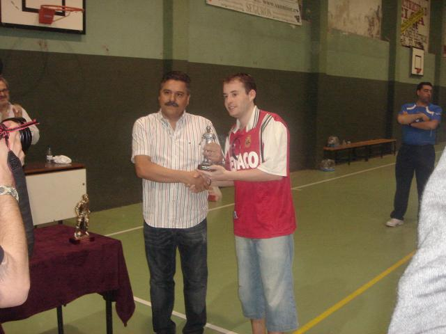 El presidente de los Antiguos Alumnos hace entrega del trofeo de subcampeon sénior a Ángel, de Churrería Núñez